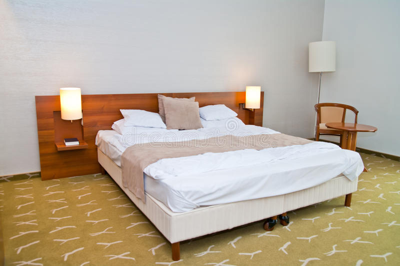 Modernes Hotelzimmer mit großem Bett lizenzfreie stockfotografie