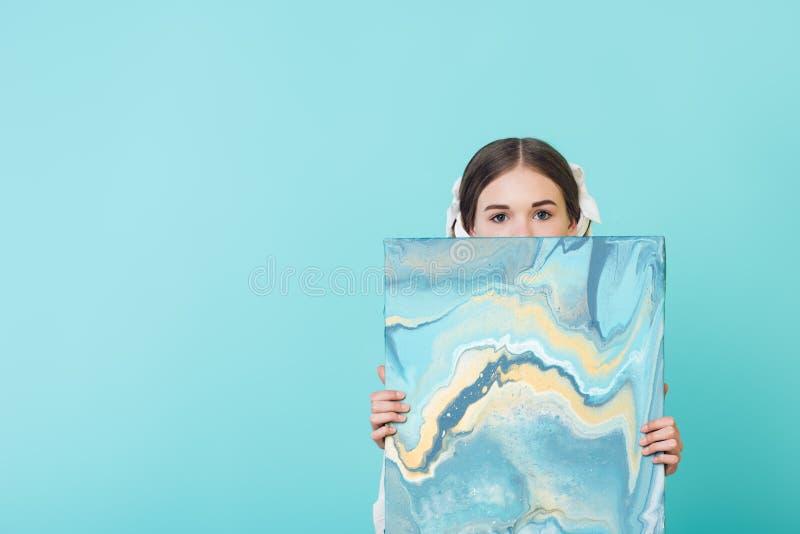 modernes Jugendmädchen, das blaues Ölgemälde hält lizenzfreie stockbilder