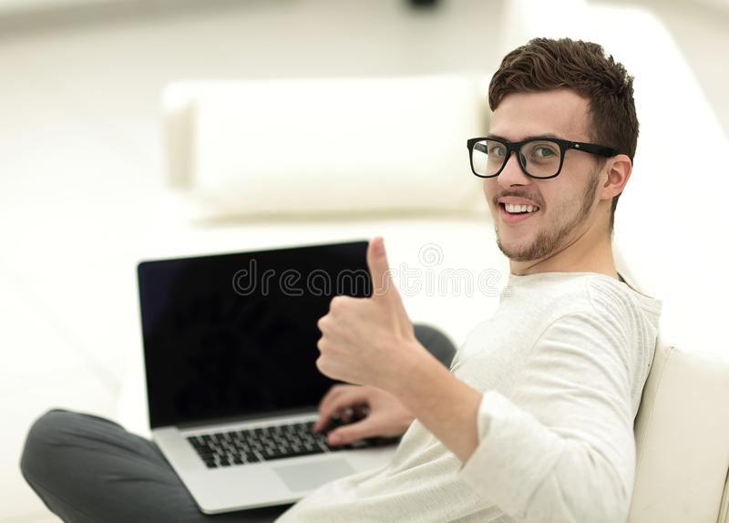 Modernes junges Sitzen vor dem offenen Laptop und Vertretung greifen oben ab stockfotografie