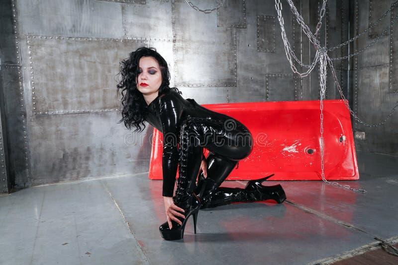 Modernes kaukasisches brunette Mädchen, das schwarzes Latex catsuit trägt und innerhalb des grauen Raumes mit metall Wänden allei stockfoto