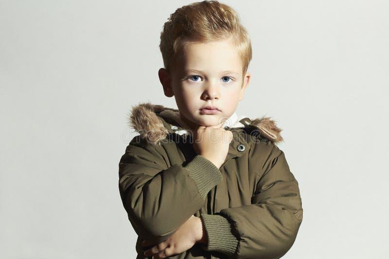 Modernes Kind im Wintermantel Kinder in der erwachsenen Kleidung kakifarbiger Parka Frisur des kleinen Jungen stockfotos