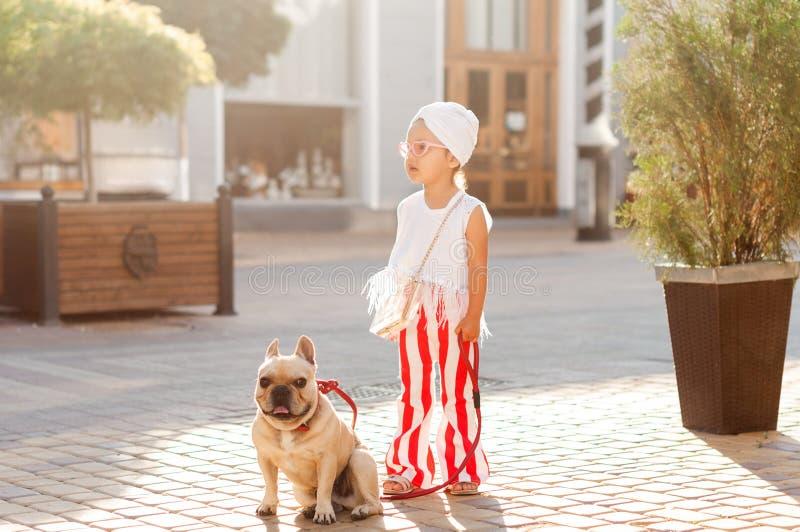 Modernes kleines Mädchen geht mit einem Hund - eine französische Bulldogge in der Stadt lizenzfreie stockfotografie