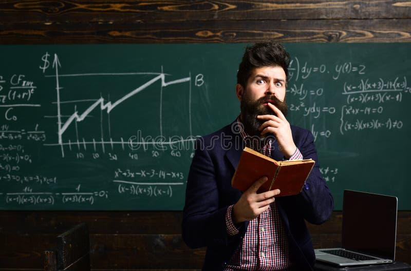 Modernes Lehrerhippie-Schreiben auf großer Tafel mit Matheformel Hochschulstudenten, die mit Büchern in der Bibliothek studieren lizenzfreie stockfotos