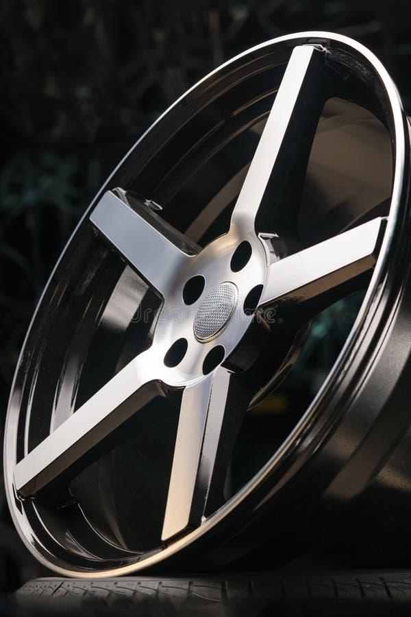Modernes Leichtmetallrad aus Aluminium, Nahaufnahme auf schwarzem Hintergrund, Speichen und Felge stockfotografie