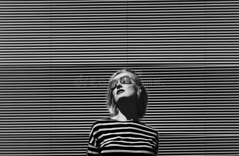 Modernes Mädchen, das in der Sonnenbrille, auf einem Metall gestreiften Hintergrund aufwirft angekleidet in gestreiftem T-Shirt T lizenzfreies stockbild