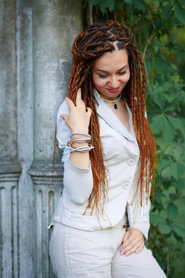 Modernes Mädchen der Dreadlocks gekleidet in der weißen Aufstellung nahe Retro- Spalten lizenzfreie stockfotos