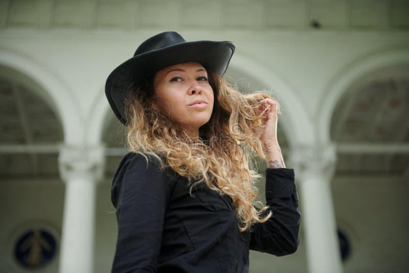 Modernes M?dchen gekleidet im schwarzen Hemd, in Hut und in breiter Hose, die nahe altem wei?em Haus aufwerfen lizenzfreie stockfotos