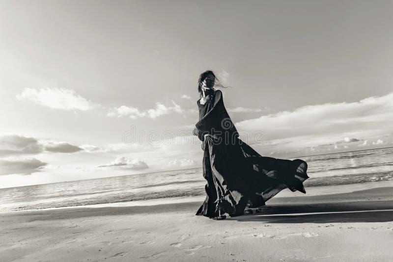 Modernes Modelltanzen der jungen Frau auf dem Strand bei Sonnenuntergang stockfoto