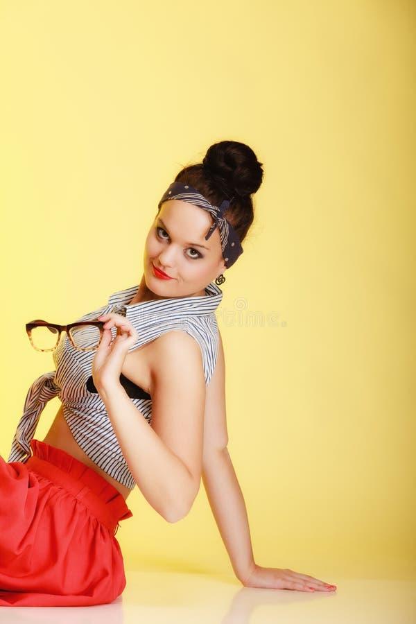 Modernes Pin-up-Girl des Porträts mit Gläsern und Brötchen auf Gelb stockfotos