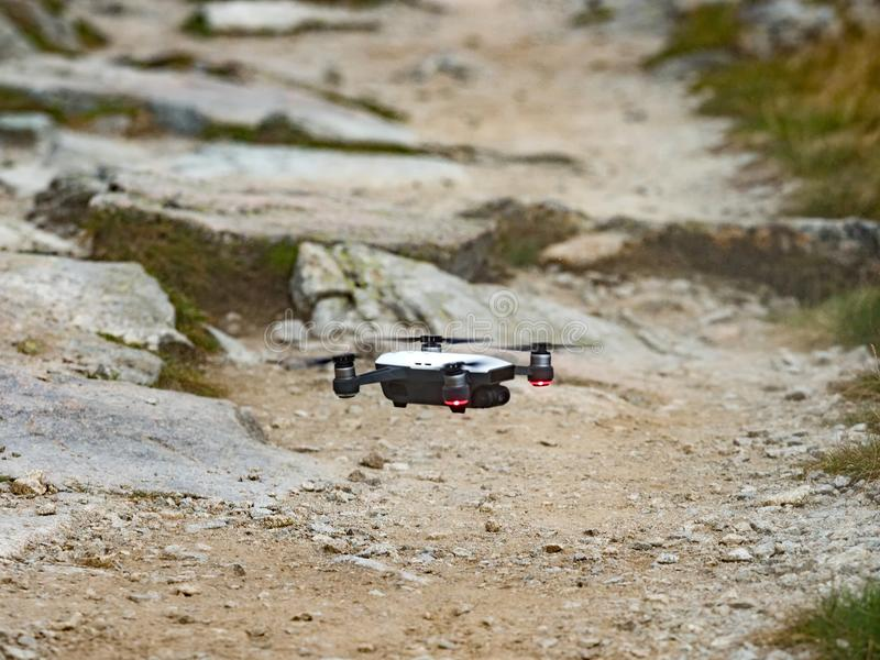 Modernes RC Brummen/Quadcopter mit Kamerafliegen im Berg Vysoke Tatry in Slowakei stockbilder