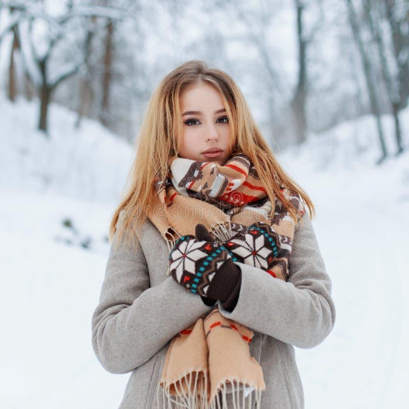 Modernes reizend junges Mädchen in einem warmen Mantel der Weinlese in den schönen woolen Handschuhen mit einem modernen Schal mi stockbild