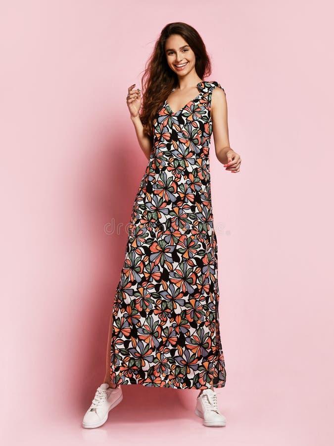Modernes schönes brunette Mädchen in einem langen geblümten Kleid zum Boden und zu den Turnschuhen, die auf einem rosa Hintergrun stockbild
