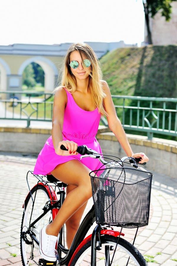 Modernes schönes junges hübsches Mädchen im rosa Kleid auf einem bicyc lizenzfreie stockfotografie