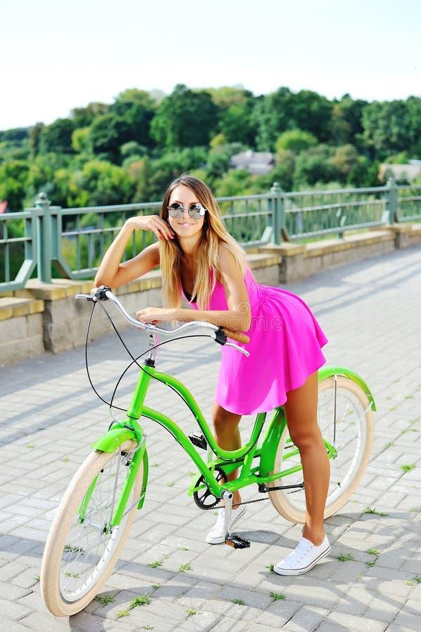 Modernes schönes junges hübsches Mädchen im rosa Kleid auf einem bicyc lizenzfreie stockfotos