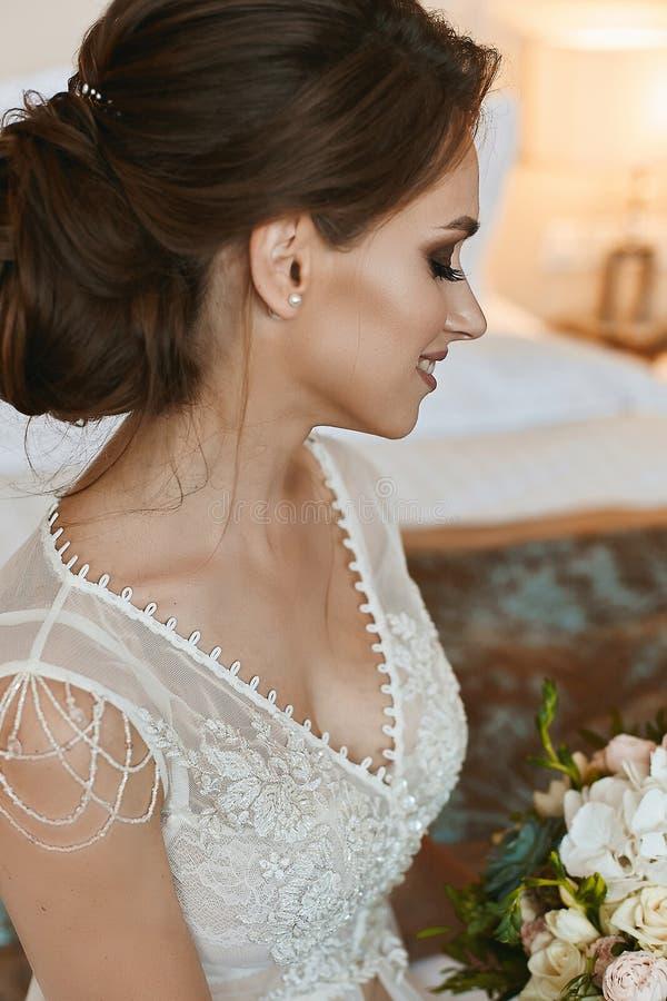 Modernes, schönes und sinnliches braunhaariges vorbildliches Mädchen mit Hochzeitsfrisur und hellem Make-up, im stilvollen Spitze lizenzfreies stockbild