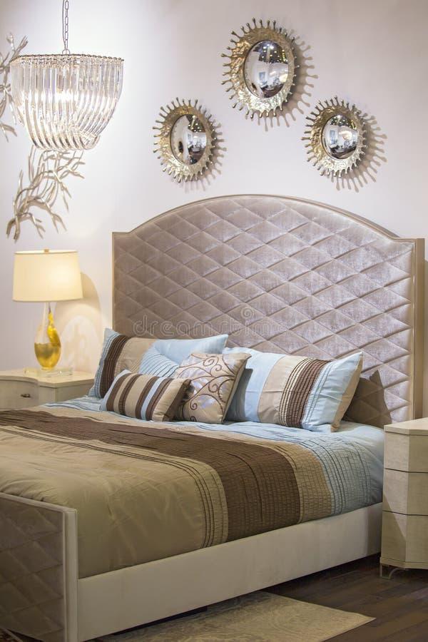 Modernes modernes Schlafzimmer, Bett, Leuchter, Spiegel auf der Wand, Nachttisch und Lampe, schöne Gewebe auf dem Bett chic lizenzfreie stockfotografie