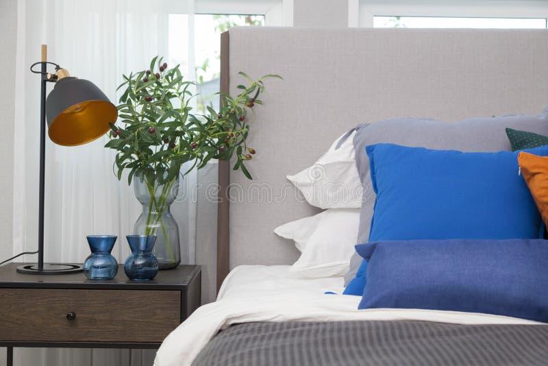 Modernes Schlafzimmer mit blauen Kissen und schwarzer Lampe lizenzfreies stockbild