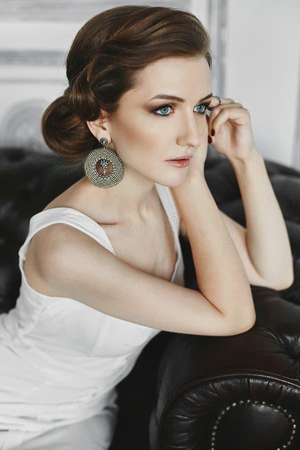 Modernes und elegantes Brunettemodellmädchen mit dem leichten Make-up große Ohrringe, im kurzen beige Kleid, sitzt auf lizenzfreies stockfoto