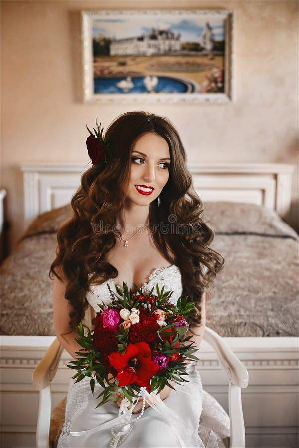 Modernes und schönes brunette vorbildliches Mädchen mit hellem Make-up und mit einem glänzenden Lächeln, in einem weißen Heiratsk stockfotos