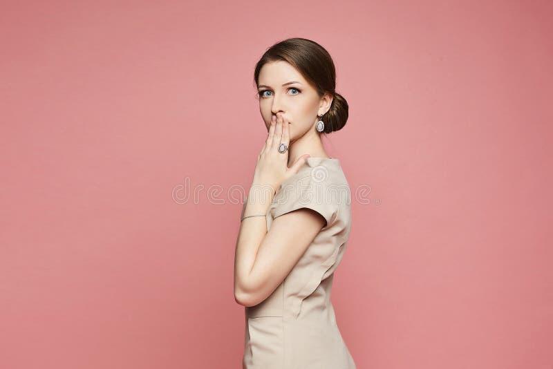 Modernes und schönes Brunettemodellmädchen im beige Kleid, werfend mit überraschtem Gesicht im Studio auf stockfotos