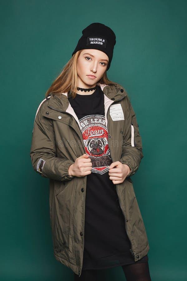 Modernes und schönes junges vorbildliches Mädchen, im schwarzen Kleid, im Hut und in der Jacke, werfend über dunkelgrünem Hinterg lizenzfreies stockfoto