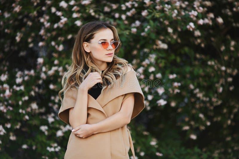 Modernes und sinnliches blondes vorbildliches Mädchen im ärmellosen Mantel und in der stilvollen Sonnenbrille lizenzfreie stockfotos