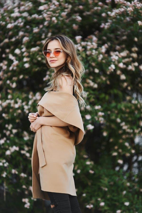 Modernes und sinnliches blondes vorbildliches Mädchen im ärmellosen Mantel und in der stilvollen Sonnenbrille stockfoto