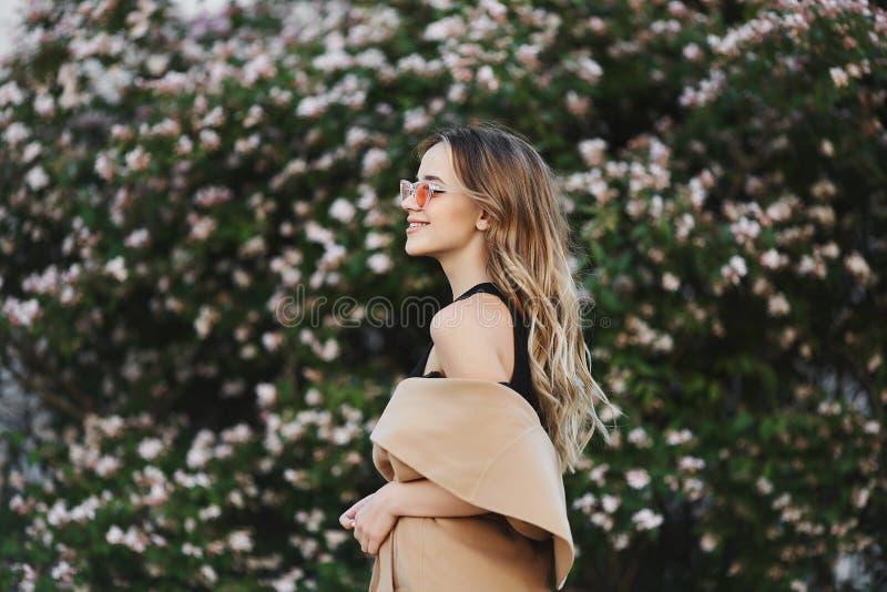 Modernes und sinnliches blondes vorbildliches Mädchen mit schönem Lächeln im ärmellosen Mantel und in der stilvollen Sonnenbrille lizenzfreies stockbild