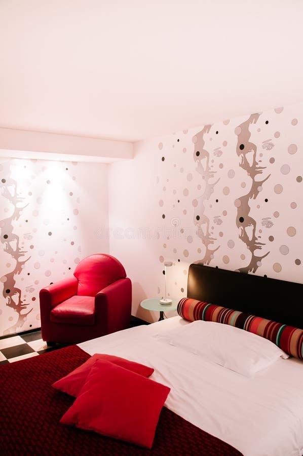 Modernes vibrierendes buntes Schlafzimmer Innen mit rotem Lehnsessel, pil stockfoto
