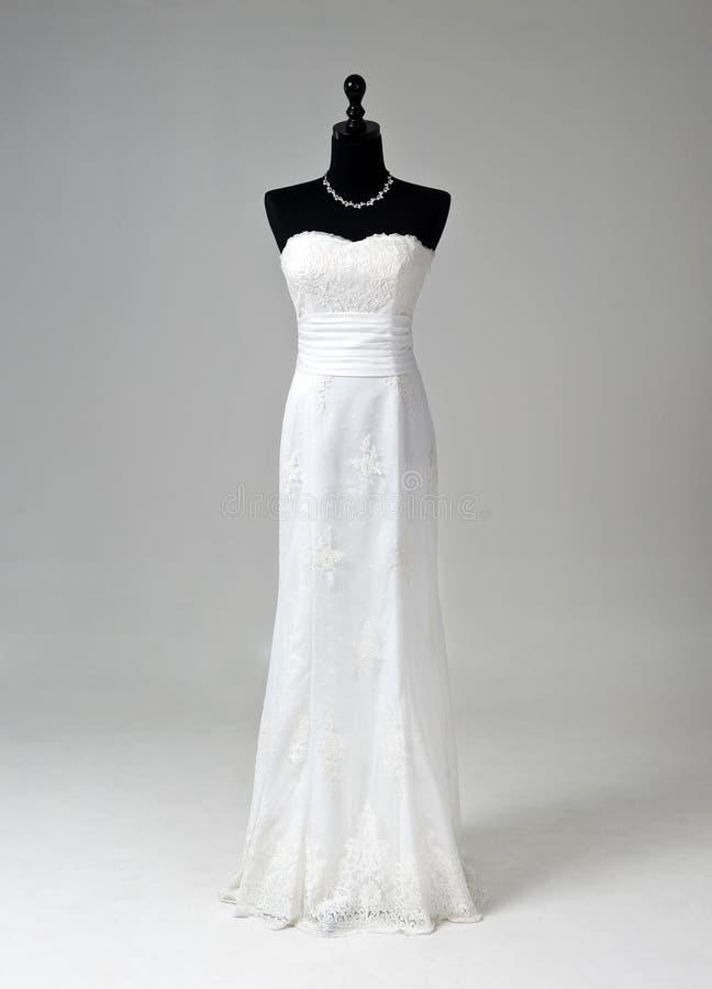 Modernes weißes Hochzeitskleid auf grauem Hintergrund stockfotografie