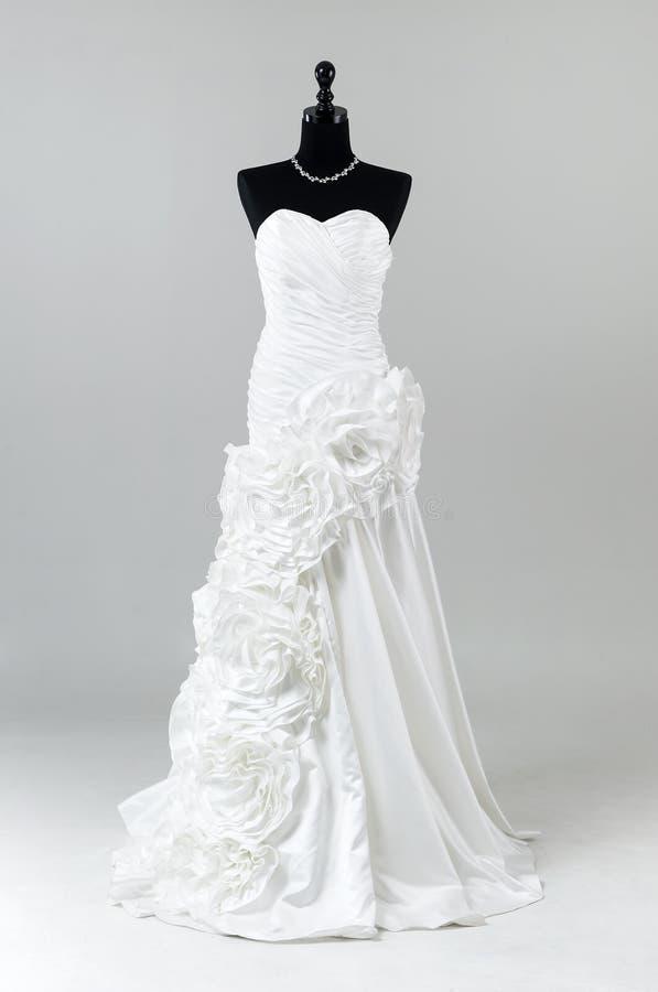 Modernes weißes Hochzeitskleid auf grauem Hintergrund stockbild