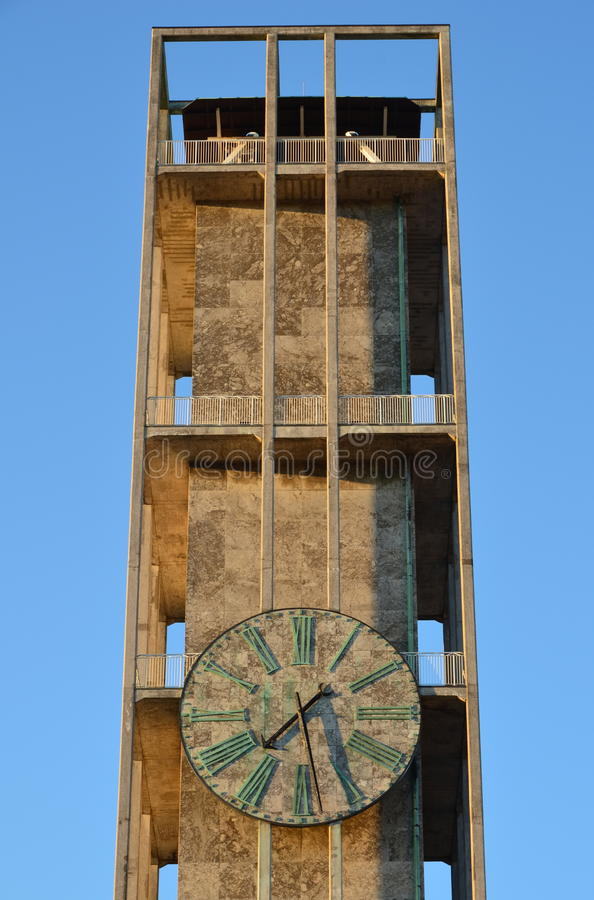 City hall tower, Aarhus, Denmark. The modernist tower of Aarhus city hall with marble clock, seen in the evening sun against the blue sky royalty free stock photos