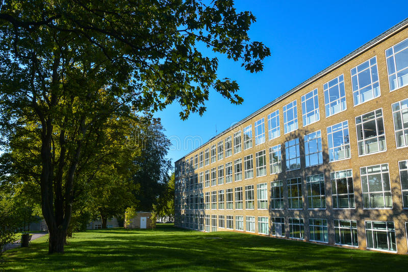 Modernistic yellow brick facade, Aarhus University. A sunny summer day creates a glittering play of sun and shade on the facade of a modernistic yellow-stone stock image