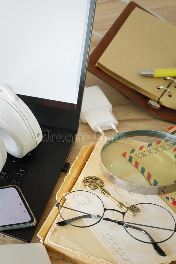 Modernity and tradition.  A laptop with a smartphone and headphones next to it A book, old-fashioned glasses, a magnifier, traditi. Onal letters and postcards stock image