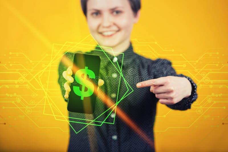 Moderno alegre da jovem mulher que mostra o smartphone móvel que aponta o dedo indicador para indicar com um sinal de dólar verde fotografia de stock royalty free
