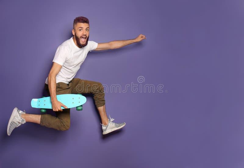 Moderno ativo com o skate que salta contra o fundo da cor fotografia de stock