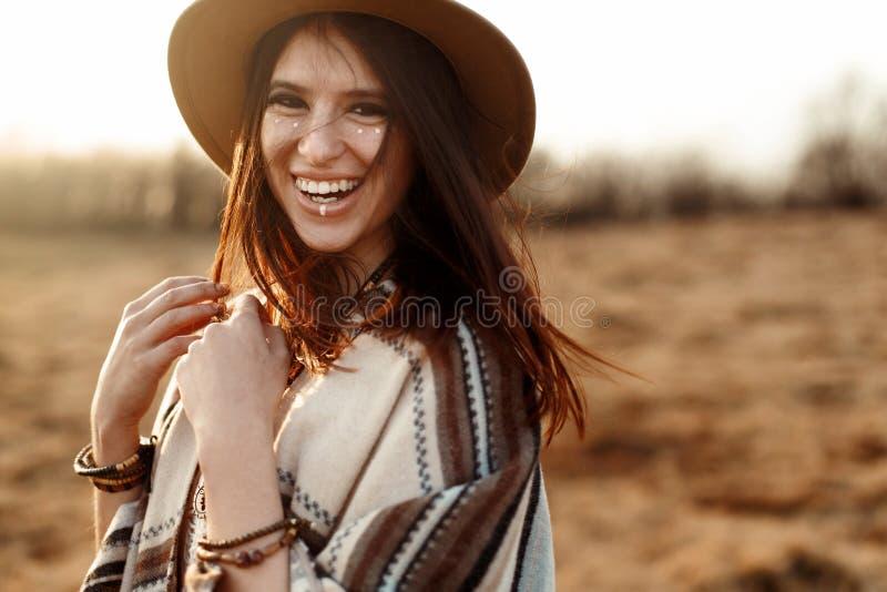 Moderno bonito da mulher do boho, poncho sorrindo, vestir chapéu e no por do sol nas montanhas, emoções verdadeiras, espaço para  fotos de stock royalty free