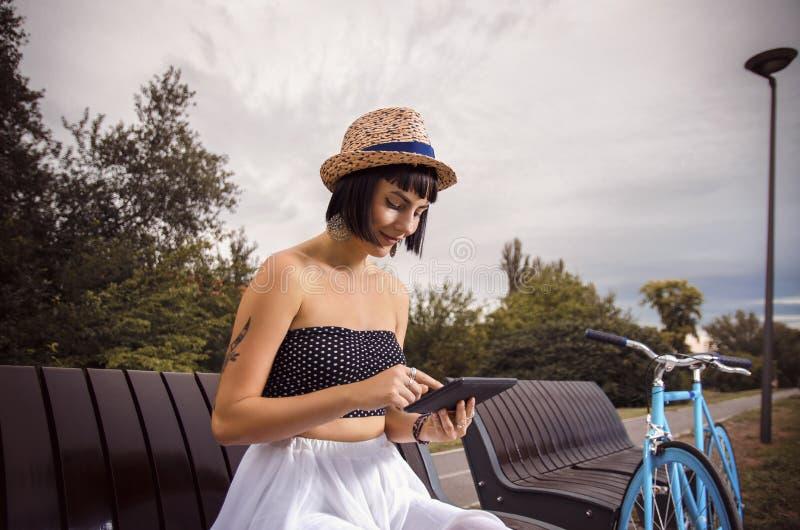 Moderno bonito jovem mulher tattooed que usa a tabuleta fotografia de stock