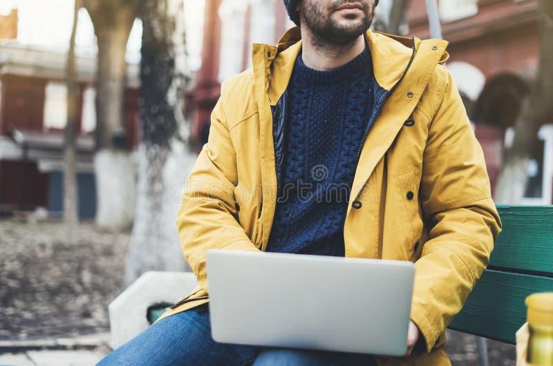 Moderno com trouxa amarela, revestimento, tampão, xícara de café thermo usando o portátil aberto do computador na rua exterior, h imagens de stock