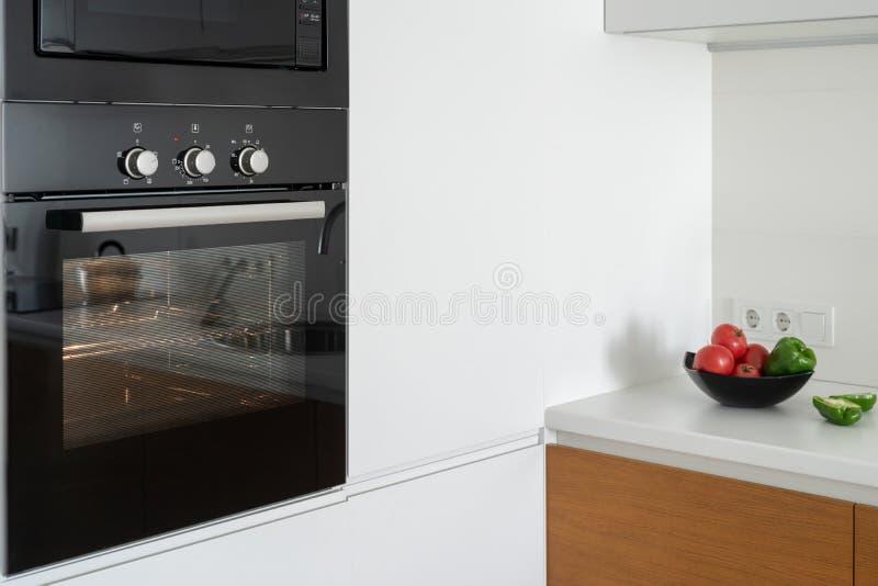 Moderno construido en horno con la puerta de cristal cerrada en la cocina blanca imagen de archivo libre de regalías