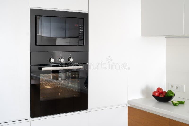 Moderno construido en horno con la puerta de cristal cerrada en la cocina blanca imagenes de archivo