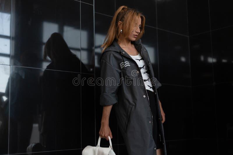 Moderno moderno da jovem mulher com um penteado em um revestimento longo na moda em vidros do vintage com um couro elegante fotografia de stock