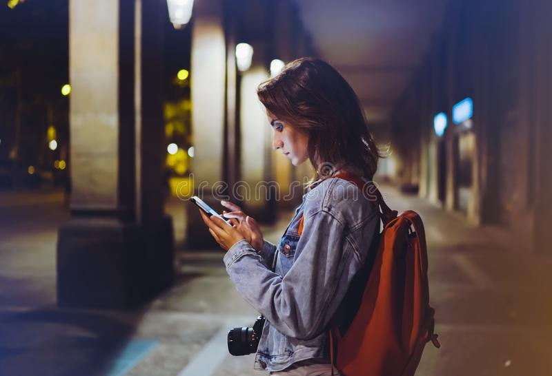 Moderno do Blogger que usa-se no telefone celular do dispositivo das mãos, mulher com trouxa que aponta o dedo no smartphone da t imagem de stock