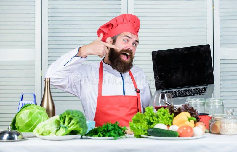 Moderno em produtos da compra do chapéu e do avental em linha Compra em linha Cozinheiro chefe do homem que procura os ingredient fotos de stock royalty free