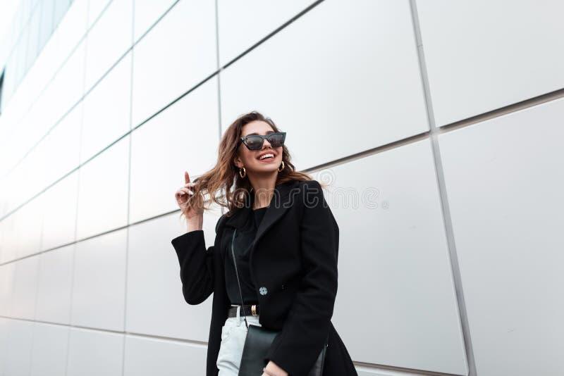 Moderno engraçado da jovem mulher em um revestimento preto à moda em um t-shirt com uma bolsa de couro na moda com um sorriso pos imagem de stock