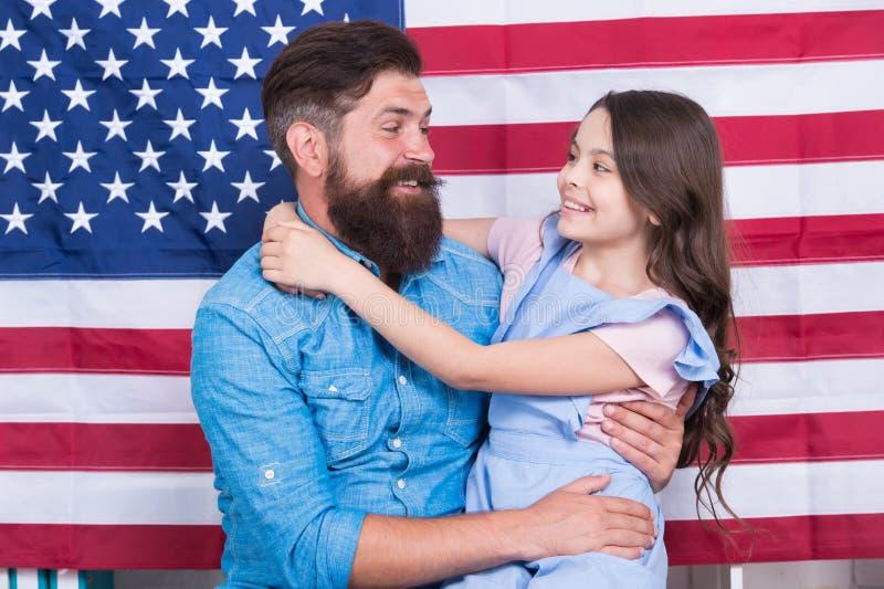 Moderno farpado do americano do pai e filha pequena bonito com bandeira dos EUA A independência é felicidade Fundo do grunge da i fotografia de stock