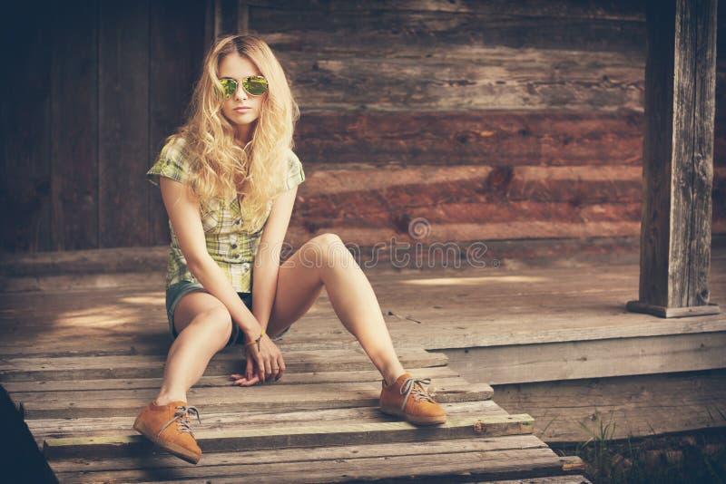 Moderno Girl Sitting modelo no patamar de madeira foto de stock royalty free