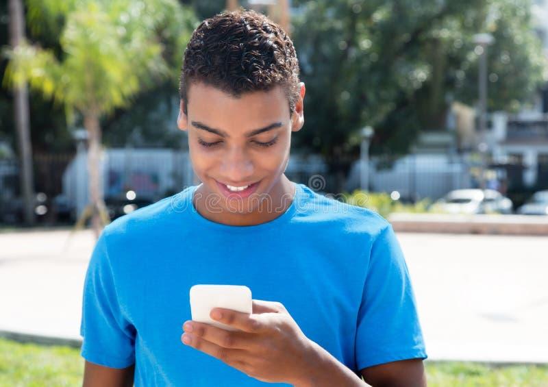 Moderno latino-americano novo que envia a mensagem pelo telefone exterior imagem de stock royalty free