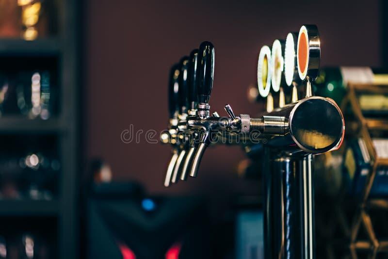 Moderno muchos golpecitos de la cerveza en la barra de la cerveza imagenes de archivo