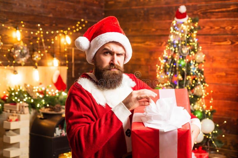 Moderno no presente vermelho da terra arrendada do chapéu de Santa Denominando o moderno de Santa com uma barba longa que levanta fotografia de stock royalty free